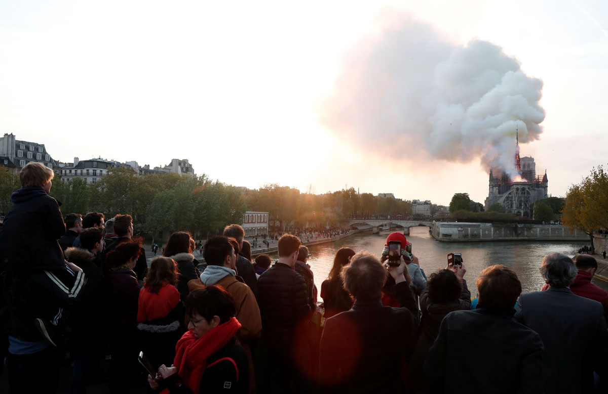 People watch from a bridge as smoke billows from Notre Dame Cathedral during a fire on April 15 2019